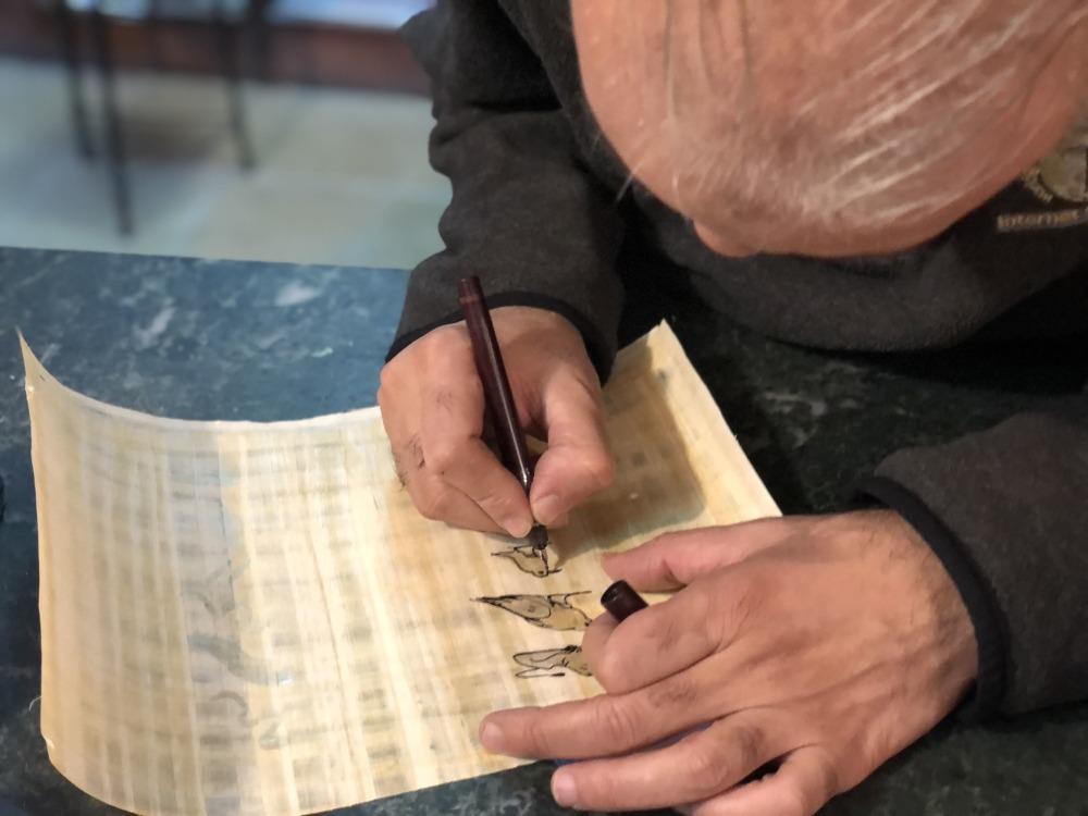 Cairota escribiendo en un pairo